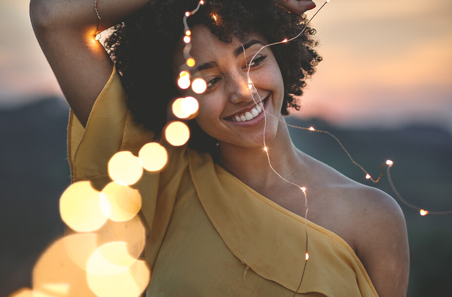 woman in yellow summer dress holding string lights over her head and smiling