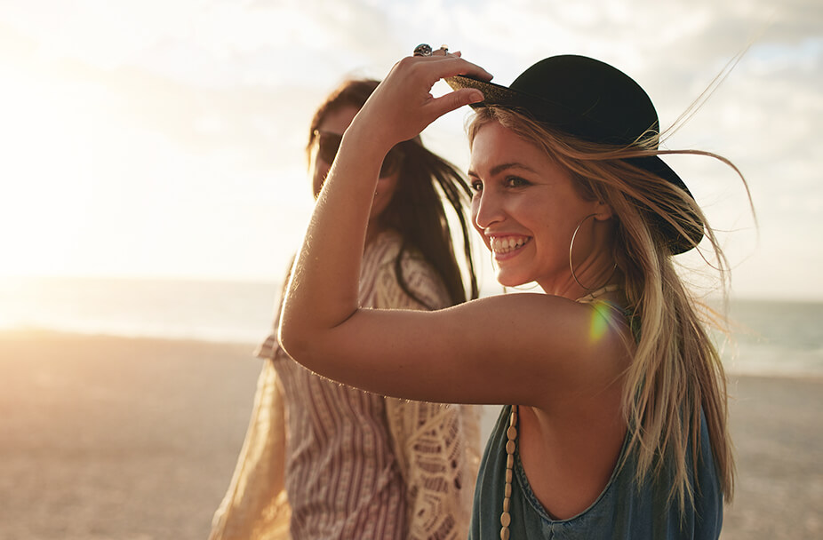 two women walking on beach and smiling while one women holds her hat to protect it from the wind